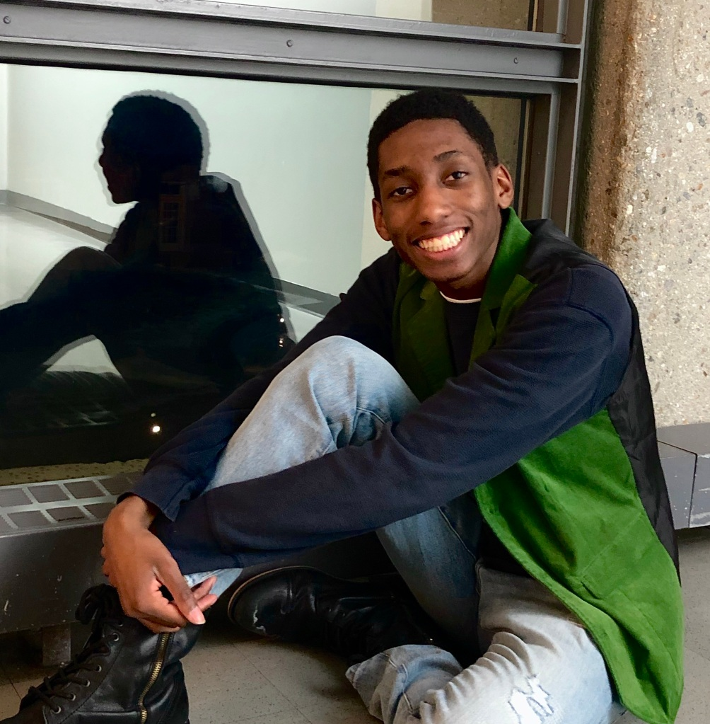 Jeffrey Steele '20. Jeffrey is sitting on the ground against a window. You can see Jeffrey's reflection in the window.